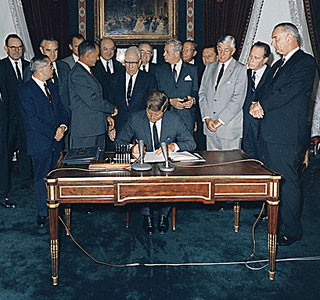 Signing of the Nuclear Test Ban Treaty, 10/07/1963: U.S. Senators look on as President John F Kennedy sits at a desk in the Treaty Room of the White House and signs the Limited test Ban Treaty.  On August 5, 1963, the Limited Test Ban Treaty was signed by the United States, Great Britain, and the Soviet Union. After Senate approval, it was signed by President Kennedy on October 7, 1963. The treaty went into effect on October 11, 1963, and banned nuclear weapons testing in the atmosphere, in outer space, and under water.