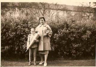 Dieter Hartmann as a child: Dieter Hartmann stands next to his mother on his first day of school holding an Easter cone full of candy.