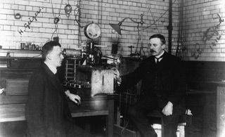 Ernest Rutherford in the lab: Ernest Rutherford sitting in his lab (right) with his assistant, Hans Geiger.