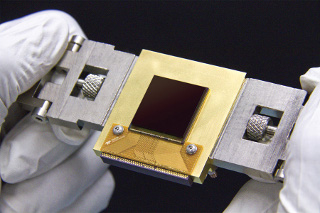 NEOCam Sensor: The Near-Earth Object Camera (NEOCam) is a mission proposed to NASA to find potentially hazardous asteroids. The mission will use a new sensor, called the NEOCam chip, that has more pixels and better sensitivity than previous generations of infrared sensors. Made of mercury, cadmium and tellurium, the new chip is about the size of a postage stamp and is optimized for detecting the faint heat emitted by asteroids circling the Sun. The NEOCam chip is the first megapixel sensor capable of detecting infrared wavelengths at temperatures achievable in deep space without refrigerators or cryogens. Judy Pipher is a member of the science team for NEOCam.