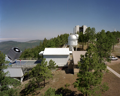 Apache Point Observatory: Apache Point Observatory in the Sacramento Mountains of New Mexico. The Sloan Digital Sky Survey's 2.5-meter telescope is on the left. White Sands National Monument is visible in the distance, above the telescope. The monitor telescope, used for calibrations, is inside the small dome to the right of center. Optical fibers for spectroscopy are pre-positioned each day in the building on the right (behind the trees). The building in the center rolls on rails to cover the 2.5-meter telescope when it is not in use.