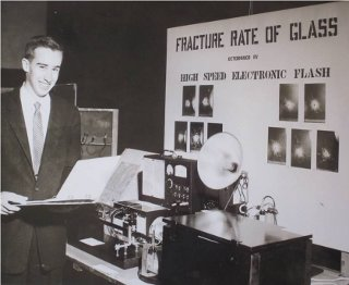 Blair Savage at the 1959 Westchester County Science Fair: The ultra high-speed flash equipment Professor Savage used to determine the fracture rate of glass. Two very closely spaced flashes of duration of one millionth of a second were obtained after the glass was broken by a bullet. The distance the crack in the glass moved between the two flashes yielded the velocity of the crack.