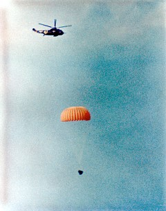 Gemini XII Splashdown on November, 11, 1966: As a helicopter hovers above, the Gemini XII spacecraft with parachute open descends to the Atlantic with astronauts Jim Lovell and Edwin Buzz Aldrin aboard.