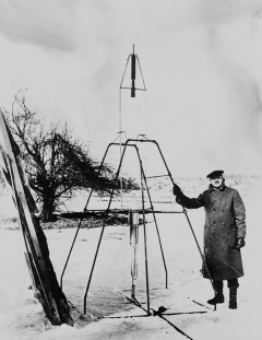 Dr. Robert H. Goddard and His Rockets: Dr. Goddard and liquid oxygen-gasoline rocket in the frame from which it was fired on March 16, 1926, at Auburn, Massachusetts. It flew for only 2.5 seconds, climbed 41 feet, and landed 184 feet away in a cabbage patch. From 1930 to 1941, Dr. Goddard made substantial progress in the development of progressively larger rockets, which attained altitudes of 7800 feet.