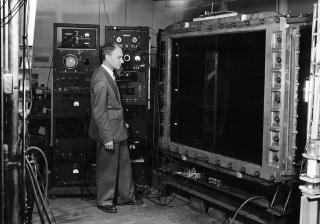 Bruno Rossi: Bruno Rossi standing before the multiplate cloud chamber used by his Cosmic Ray Group at MIT, 1954.