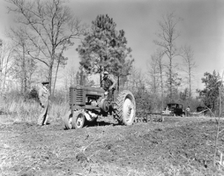 Preparing plant bed, tobacco series, Dinwiddie County: Modern farming requires machinery such as the tractor (foreground) and truck (background) seen in this image.  Learning to use and maintain the equipment often spurs interest and expertise in how machines work.