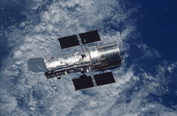 Photo of Hubble Space Telescope with the Earth in the background.